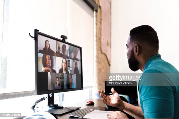 businessman participates in virtual staff meeting - staff meeting stock pictures, royalty-free photos & images