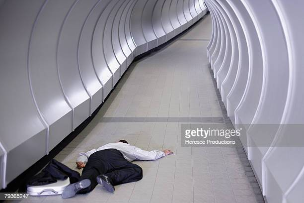 businessman passed out in corridor - out of context stock pictures, royalty-free photos & images