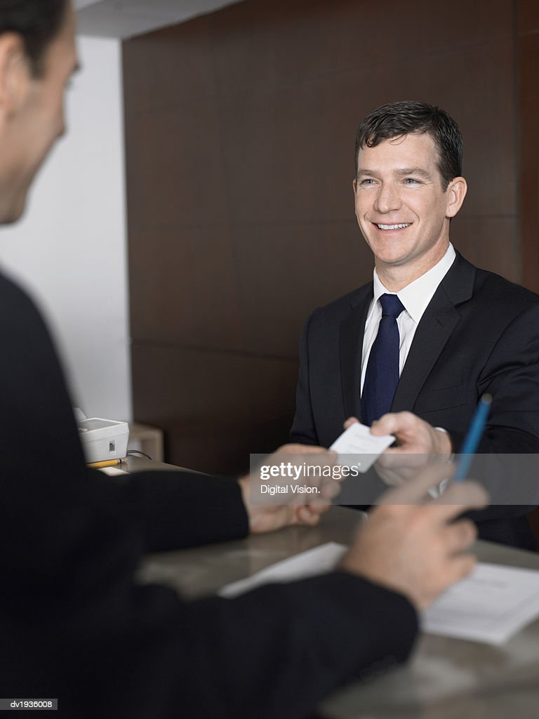 Businessman Passes a Business Card at a Reception Desk : Stock Photo
