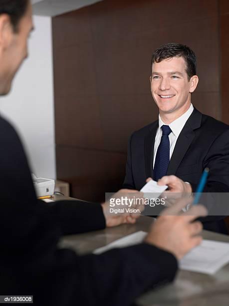 Businessman Passes a Business Card at a Reception Desk