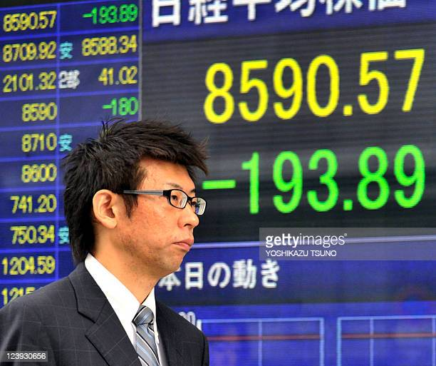 A businessman passes before a share prices board in Tokyo on September 6 2011 Asian shares tumbled on September 6 with Tokyo hitting a twoyear low...