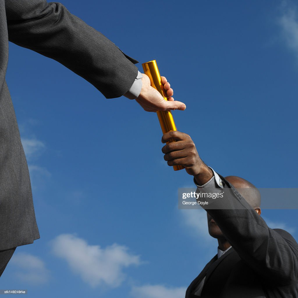 businessman passing baton to businessman, low angle view : Stock Photo