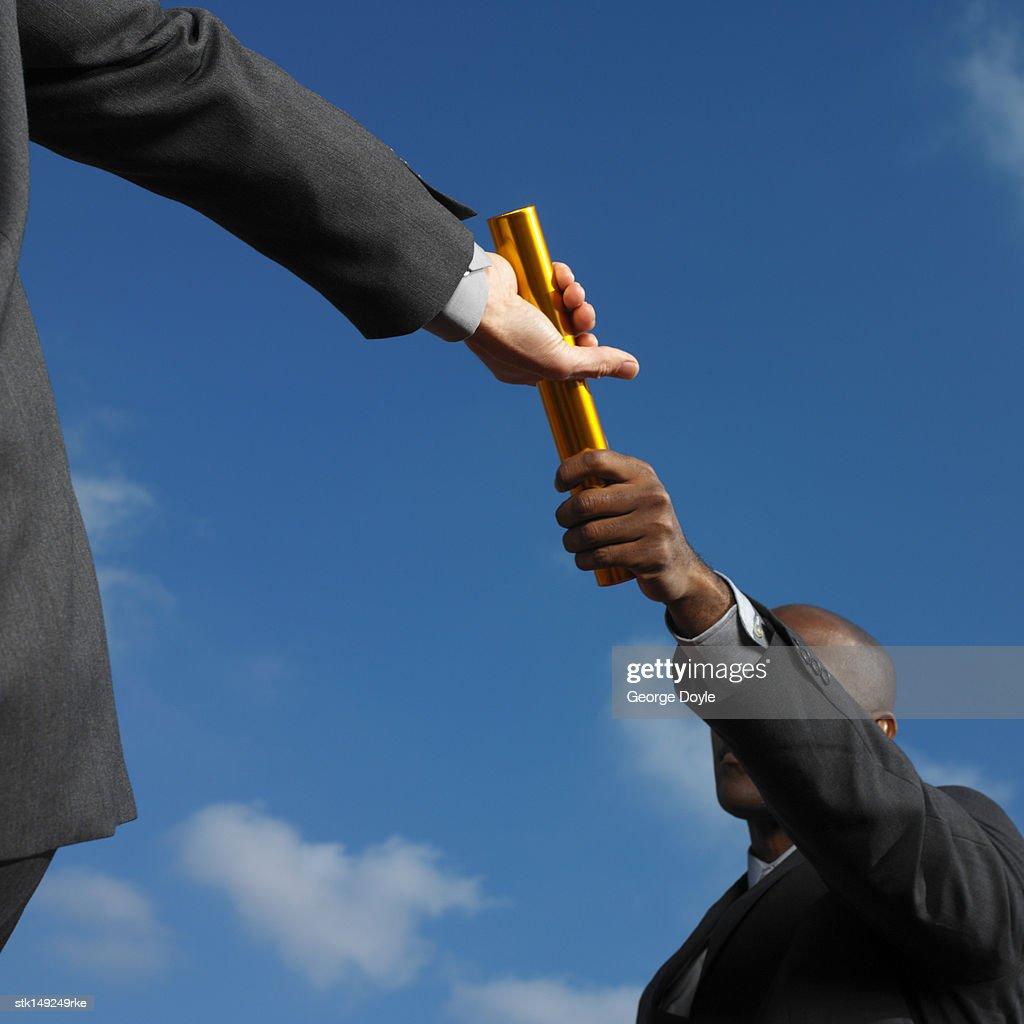businessman passing baton to businessman, low angle view : ストックフォト