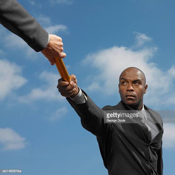 businessman passing baton to businessman low angle view