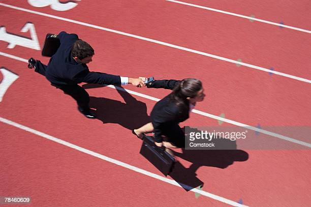 Businessman passing businesswoman cell phone in relay race