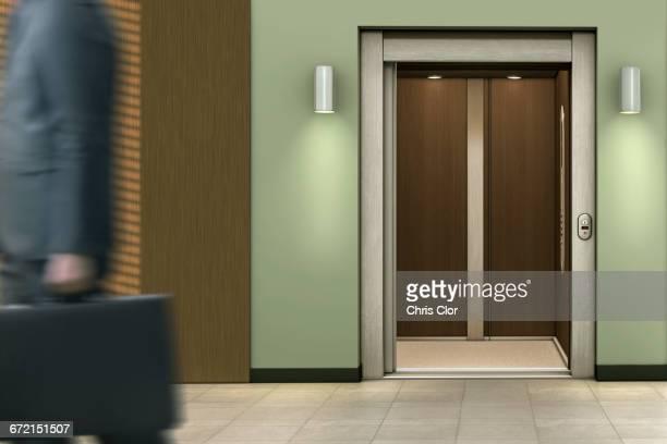 businessman passing open elevator - elevador imagens e fotografias de stock
