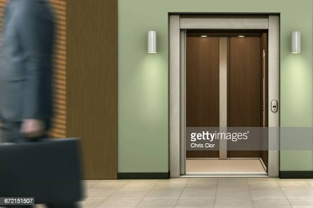 Businessman passing open elevator
