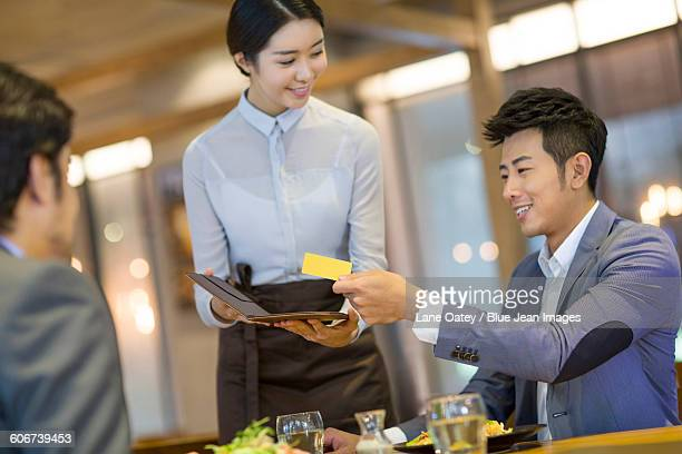 Businessman paying bill by credit card in restaurant