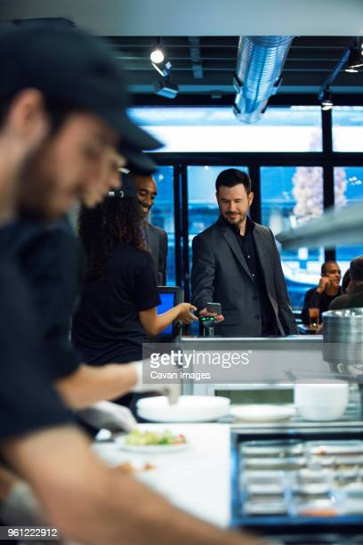 Businessman paying bill through smart phone while standing in restaurant