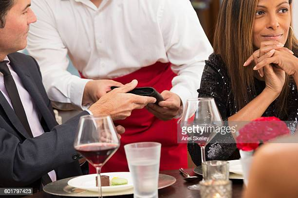 Businessman paying check at restaurant