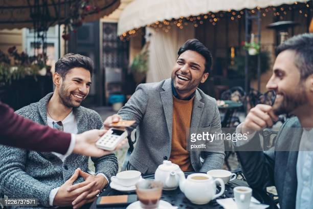 businessman paying the bill in cafe with a credit card - smart casual stock pictures, royalty-free photos & images
