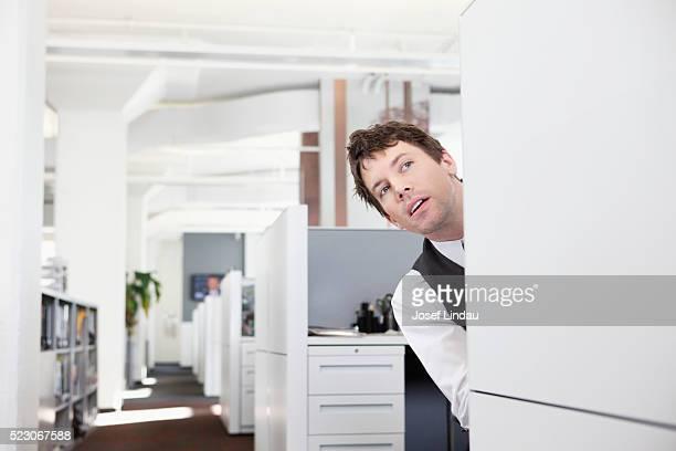 Businessman peeking around a cubicle wall