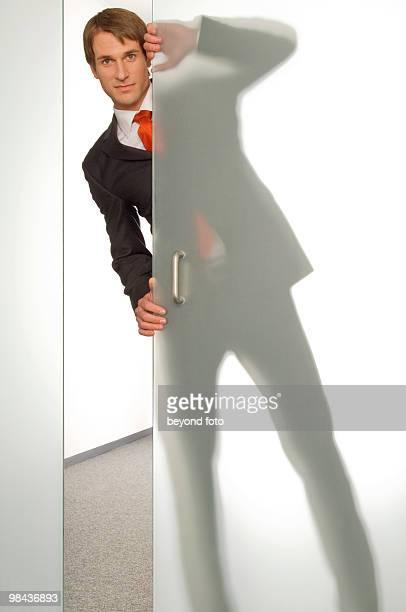 businessman peeking behind half open glass door