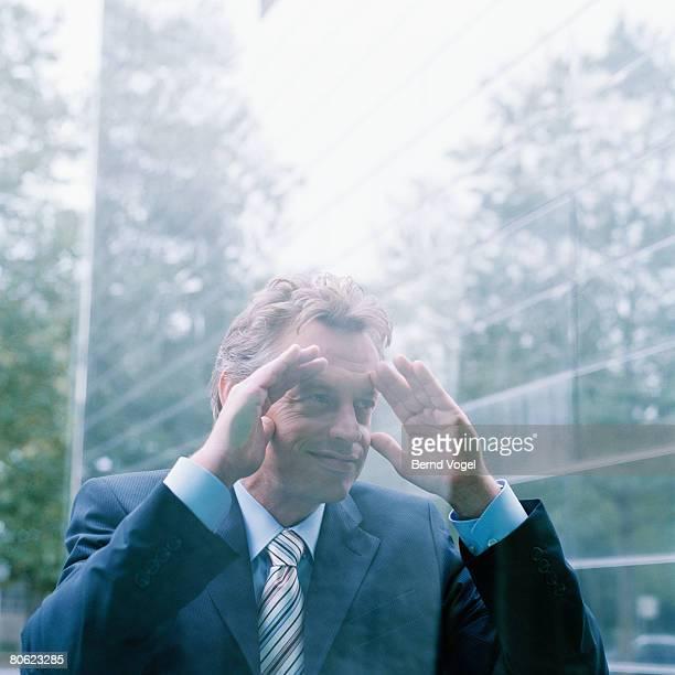Businessman peering in window