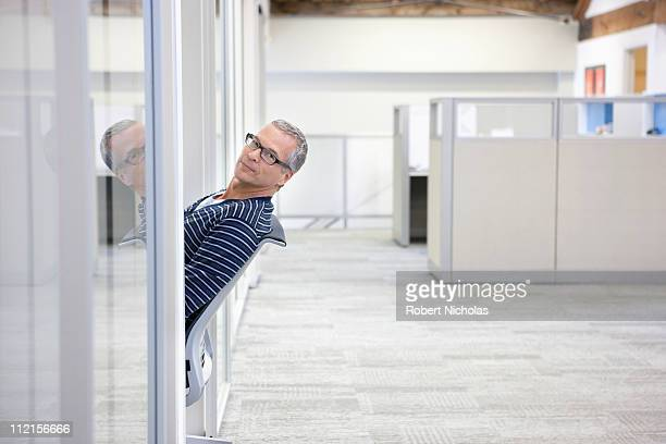 Businessman peering out of office