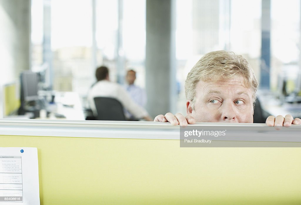 Businessman peering over cubicle wall : Stock Photo