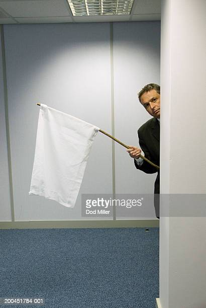 Businessman peering round wall holding white flag, portrait