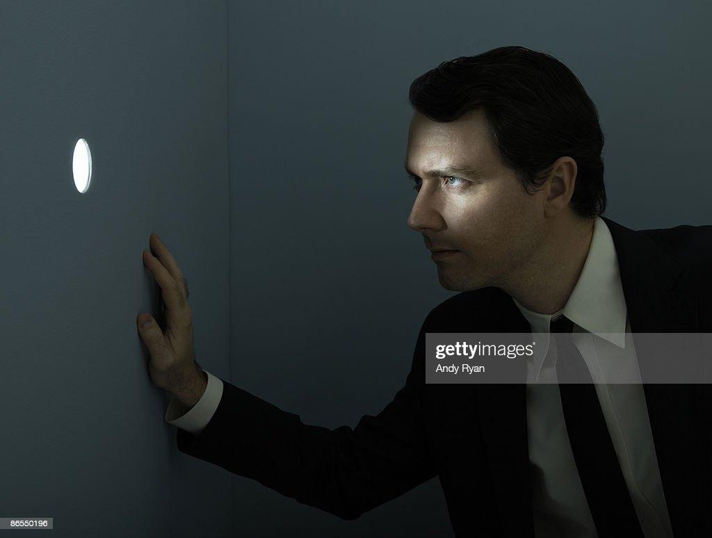 Businessman peering through illuminated peep hole. : Stock Photo
