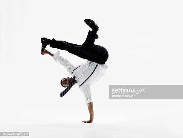 Businessman performing handstand on one hand and grabbing foot