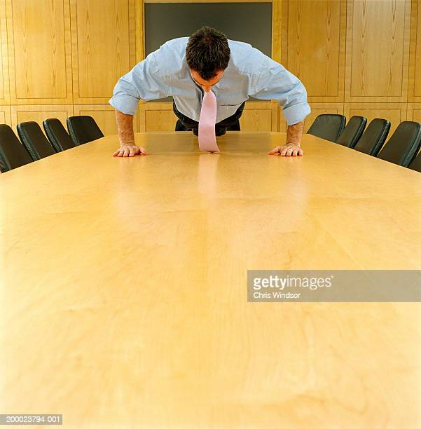 Businessman performing press up on boardroom table