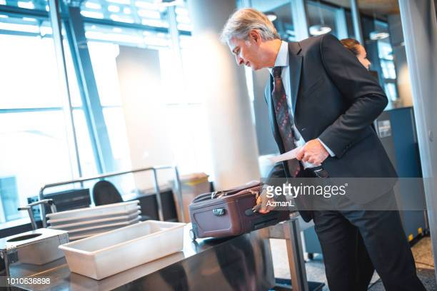 businessman picking baggage on counter at airport - security check stock photos and pictures