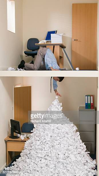 Businessman Picking Piece of Paper From Top of Pile
