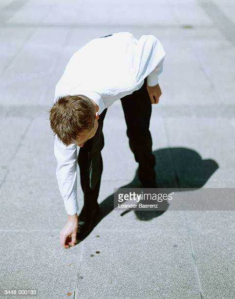 businessman picking up coin - bending over stock pictures, royalty-free photos & images