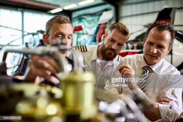 businessman, pilot and mechanic examining helicopter engine in airplane hangar - transportation occupation stock pictures, royalty-free photos & images