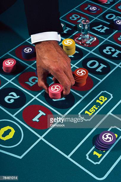 Businessman placing chips on craps table