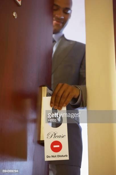 Businessman placing do not disturb sign on doorknob