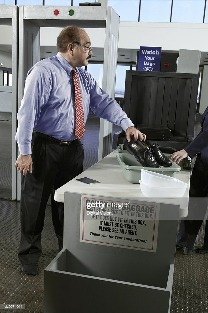 Businessman Placing Shoes in a Container at Airport Customs : Stock Photo