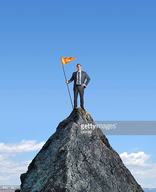 Businessman Planting A Flag On Top Of Mountain