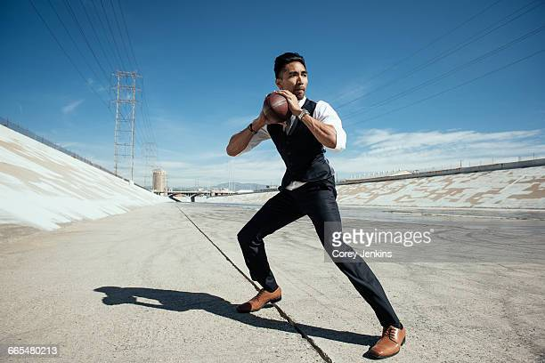 Businessman playing american football on Los Angeles river, California, USA