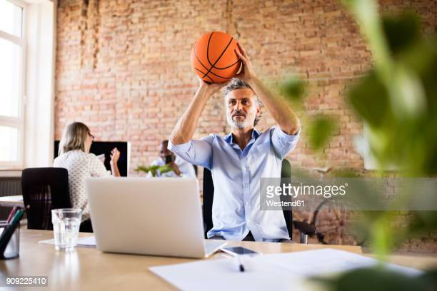 Businessman playing basketball in office with colleagues in background