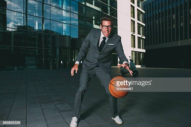 Businessman playing basketball outside office building