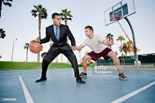businessman playing basketball with friend - dribbling sports stock pictures, royalty-free photos & images