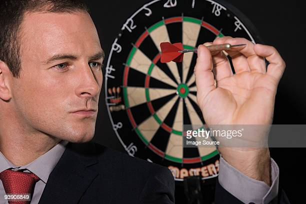Businessman playing darts