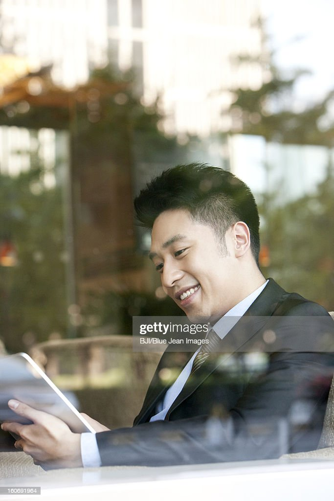 Businessman playing digital tablet in cafe : Stockfoto