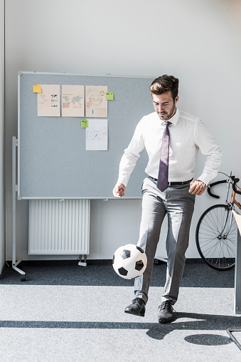 Businessman playing football in office - gettyimageskorea