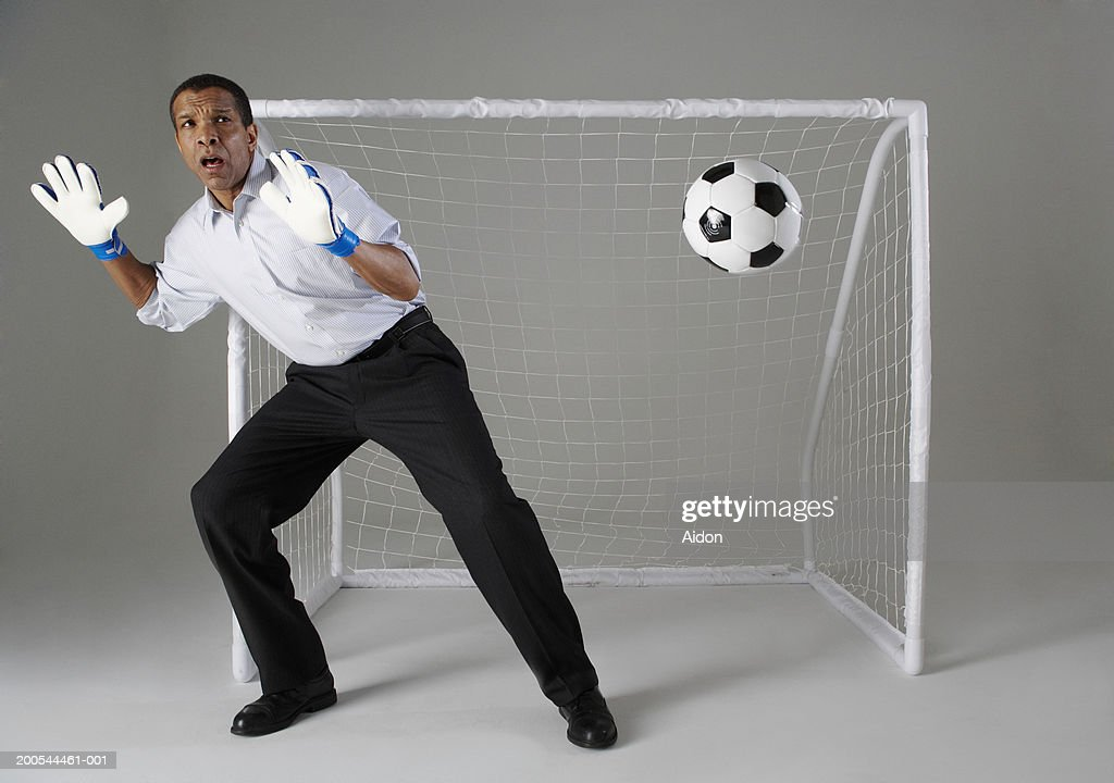 Businessman playing goalkeeper, missing ball, studio shot : Stock Photo