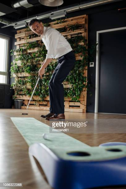businessman playing golf in office - miniature golf stock photos and pictures