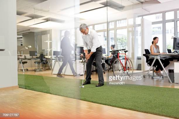 Businessman playing golf in office