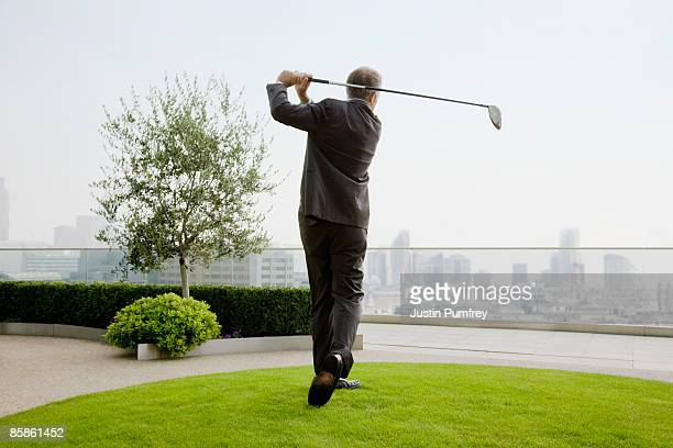 Businessman playing golf on rooftop, rear view