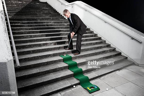 businessman playing golf on stairway - putting stock pictures, royalty-free photos & images