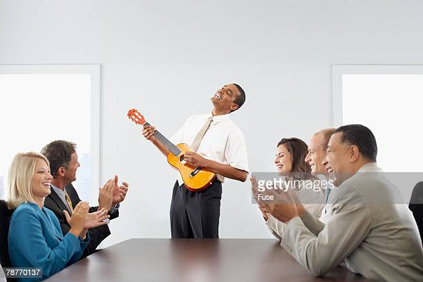 Businessman Playing Guitar in a Business Meeting