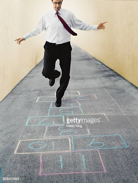 businessman playing hopscotch - hopscotch stock pictures, royalty-free photos & images