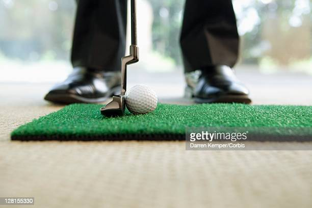 Businessman playing mini golf ball, low section