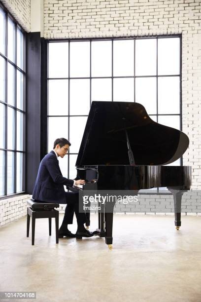 businessman playing piano - pianist stock pictures, royalty-free photos & images