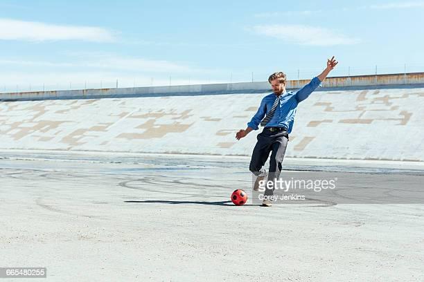 businessman playing soccer on los angeles river, california, usa - chutar imagens e fotografias de stock