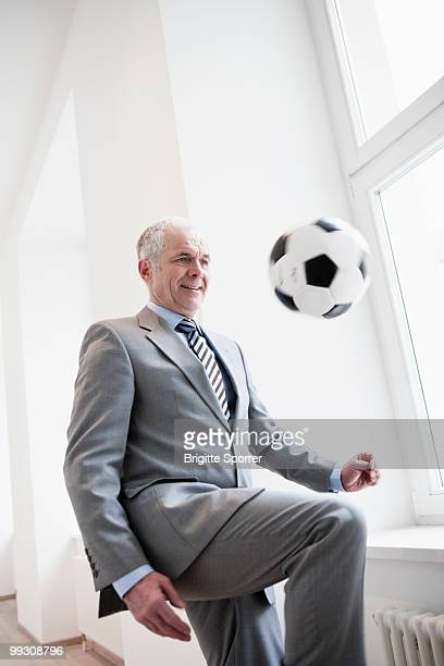 Businessman playing soccer